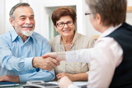 Photo pour Couple senior souriant et en agitant la main avec le conseiller financier - image libre de droit