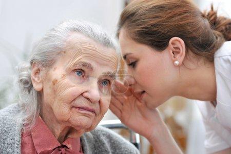 Photo pour Infirmière parle dans l'oreille d'une femme senior - image libre de droit