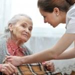 Female nurse is taking care of the senior woman...