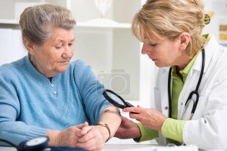 Photo pour Médecin féminin examinant une taupe chez le patient - image libre de droit