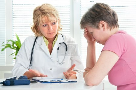 Mid adult woman talking to doctor about her diagno...