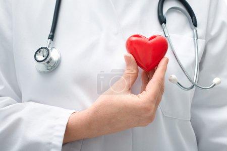 Photo pour Femme médecin avec le stéthoscope tenant coeur - image libre de droit