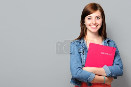 Photo for Young woman holding job application on grey background - Royalty Free Image