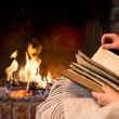 Hands of woman reading book by fireplace...