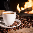 Cup of hot coffee and coffee beans near fireplace...