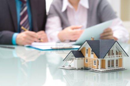 Photo pour Homme d'affaires signe un contrat derrière maison modèle architectural - image libre de droit