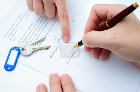 Photo for Rental agreement form with signing hand and keys and pen - Royalty Free Image