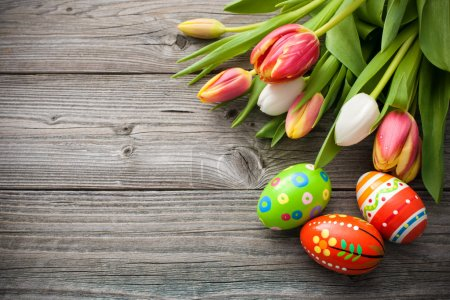 Photo for Easter eggs with tulips on weathered wooden background - Royalty Free Image