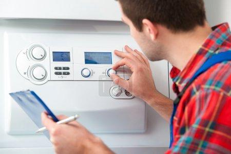 Foto de Técnico de mantenimiento de la caldera de gas para agua caliente sanitaria y calefacción - Imagen libre de derechos