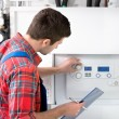 Technician servicing the gas boiler for hot water ...