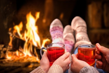 Photo for Couple relaxing with mulled wine at romantic fireplace on winter evening - Royalty Free Image