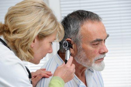 Photo pour Médecin ORL à la recherche à l'oreille du patient avec un instrument - image libre de droit