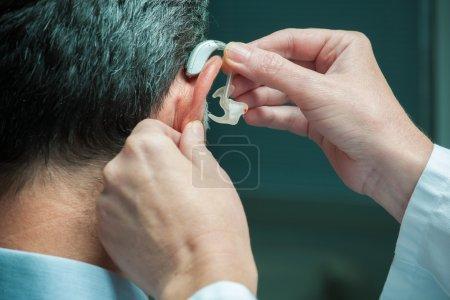 Photo pour Docteur insertion prothèse auditive dans l'oreille de la personne âgée - image libre de droit