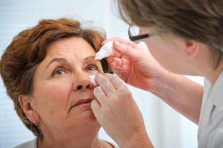 Photo pour Médecin aide le patient et donne les gouttes pour les yeux - image libre de droit