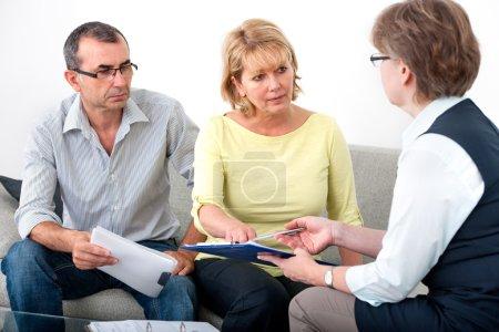 Photo pour Couple senior, obtenir des conseils financiers de conseiller à la maison - image libre de droit