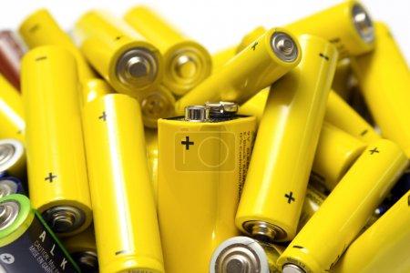 Photo pour Vieilles piles jaunes sur fond blanc prêtes à être éliminées et recyclées - image libre de droit