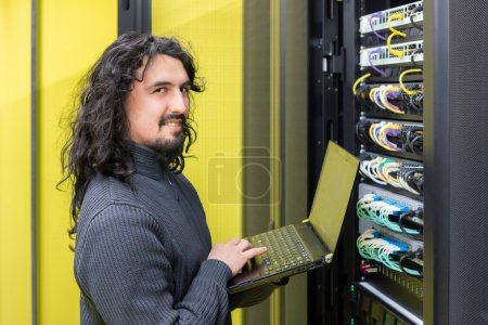 Man working with servers in data center