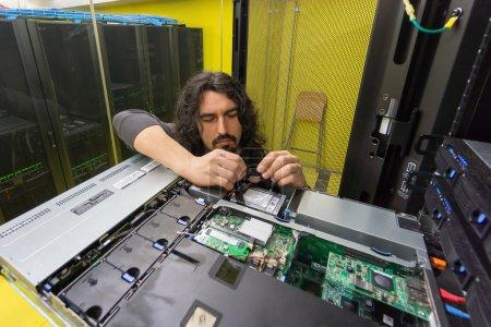 Photo pour Jeune ingénieur technicien professionnel réparateur serveur dans la salle informatique - image libre de droit