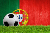 Soccer ball on grass with Portugal flag background
