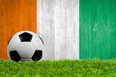 Soccer ball on grass with Ivory Coast flag background