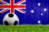 Soccer ball on grass with Australia flag background