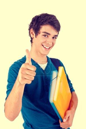 Photo pour Jeune étudiant heureux montrant pouces vers le haut sur fond blanc - image libre de droit