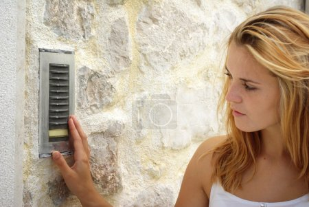 Woman using house intercom, outdoor