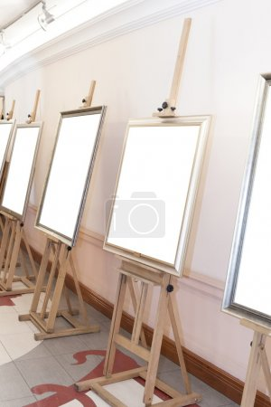 Corridor with blank frames on painting easel