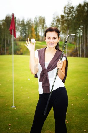 Photo for Smiling young woman golf player on green with ball and club near cup flag - Royalty Free Image