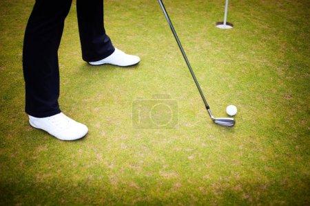 Golf player training putting ball on green