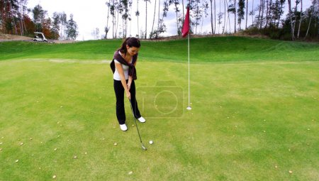 Young woman golf player on green, preparing to shot