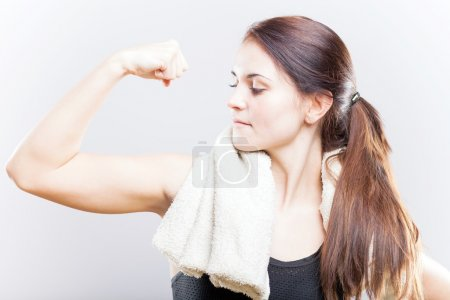 Young fit woman looking at her biceps after training