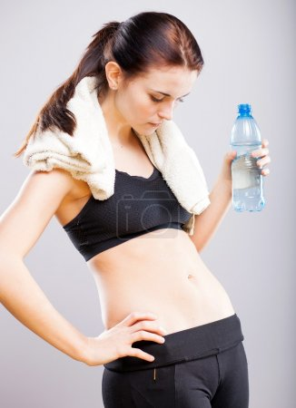 Woman looking at her flat stomach after training