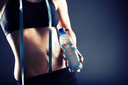 Sweaty woman after training holding water bottle