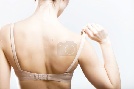 Woman holding a skin colored bra strap