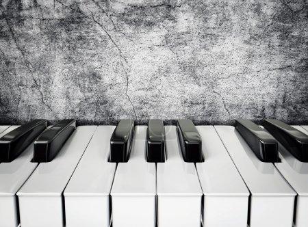 Photo pour Touches du piano noir et blancs sur un mur de stuc - image libre de droit