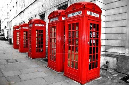 Photo pour London Red Telephone Boxes on the Street. Bâtiments noirs et blancs et rue avec cabines téléphoniques Red London - image libre de droit
