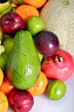 Foto de Tema de frutas tropicales frescas - foto estudio vertical. papaya fresca, ciruela, Granada, mandarina, plátano y más. - Imagen libre de derechos
