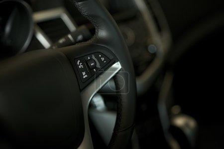 Photo pour Volant de voiture et de l'intérieur de la voiture. intérieur sombre avec peu de lumière. boutons multimédia sur le volant de la voiture. des intérieurs de véhicules de collection photo. - image libre de droit