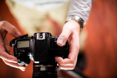 Photo pour Appareil photo professionnel dans les mains du photographe. thème de la photographie. vue de dessus - mains mâles. collection de photos de technologie. - image libre de droit