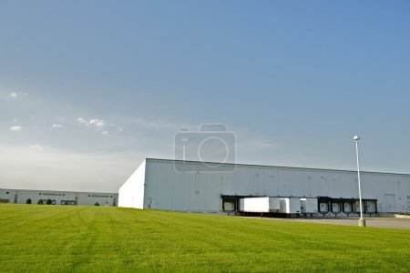 Photo for Industrial Zone - Warehouses with Truck Gates and Green Field. Industrial Collection. - Royalty Free Image
