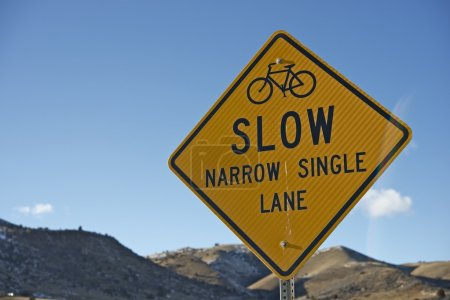 Photo for Slow Sign for Bikers. Slow - Narrow Single Lane Yellow Traffic Sign Closeup. - Royalty Free Image
