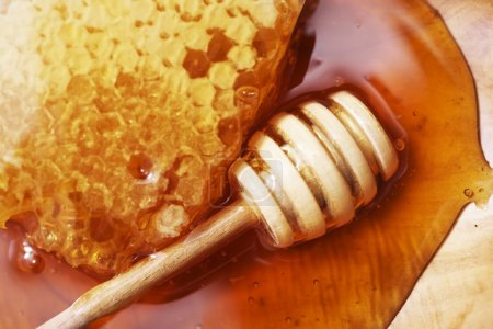 Honeycomb with Wooden Dipper on Wooden Plate Close...