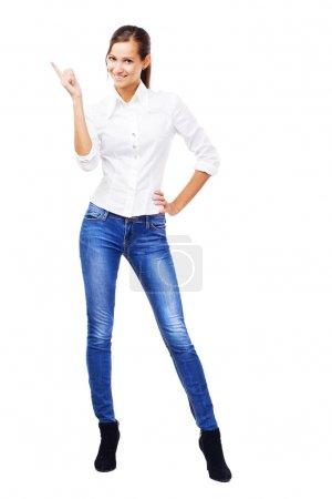 Photo pour Belle femme en chemise blanche et jean bleu pointant vers le copyspace, isolée sur fond blanc - image libre de droit