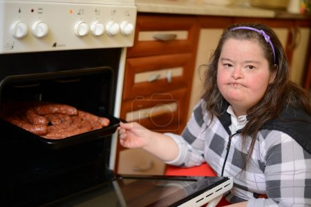 Attractive down syndrome woman cocking in the kitchen