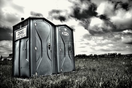 Photo for Two portable bathrooms on a cloudy overcast day - Royalty Free Image