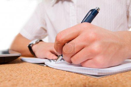 Photo pour Gros plan d'une main d'étudiant écrit dans le cahier d'exercices - image libre de droit