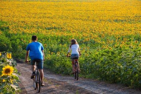 Teen couple riding bike in sunflower field