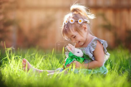 Photo for Cute little girl with a bunny rabbit has a easter at green grass background - Royalty Free Image