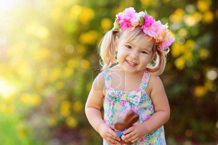 Photo pour Mignonne fille de Pâques avec lapin chocolat en plein air - image libre de droit